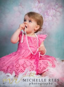 library, books, reading, glasses, study, crossed, bookshelf, toys, photo props, child, daughter, children, girl, model, granddaughter, photoshoot, michelle rees photography, toddler, baby, pink, beads, necklace, turquoise, white, feather boa, boa, feathers